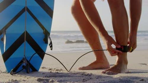 Man tying surfboard leash at beach in the sunshine