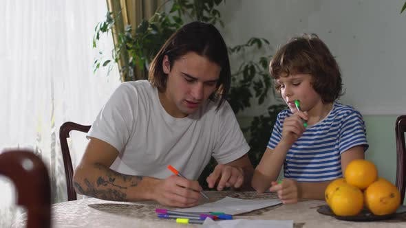 Two Brothers One Adult and One Small Boy Sitting on the Table and Handsome Man Draw Pictures