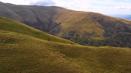Trail bikers ride on off road trail by mountain bike in autumn. Friends riding mountain bike