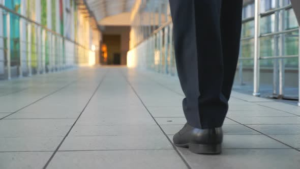 Thumbnail for Feet of Successful Businessman Walking in Hall of Terminal and Pulling Suitcase on Wheels. Legs Of