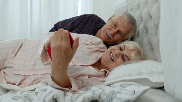 Thumbnail for Senior Grandparents Couple Lying in Bed. Woman Getting Nervous About Man Spying Into Mobile Phone