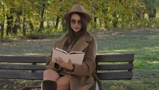 Thumbnail for Intelligent Caucasian Woman in Sunglasses and Brown Hat Sitting on Bench and Reading the Book