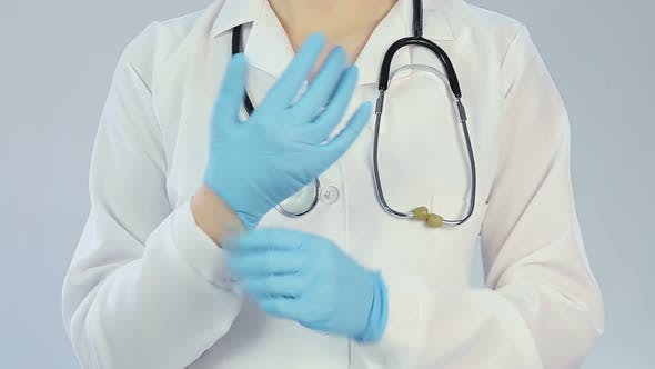 Thumbnail for Woman doctor putting on medical gloves before examining patient, healthcare