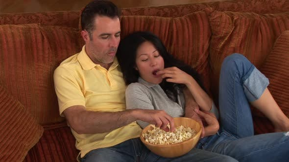 Thumbnail for Young couple on couch with popcorn watching TV