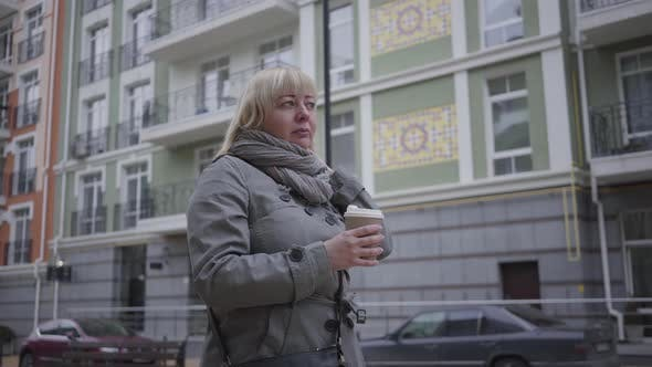 Thumbnail for Confident Senior Caucasian Woman Walking Along City Street and Drinking Coffee. Relaxed Female