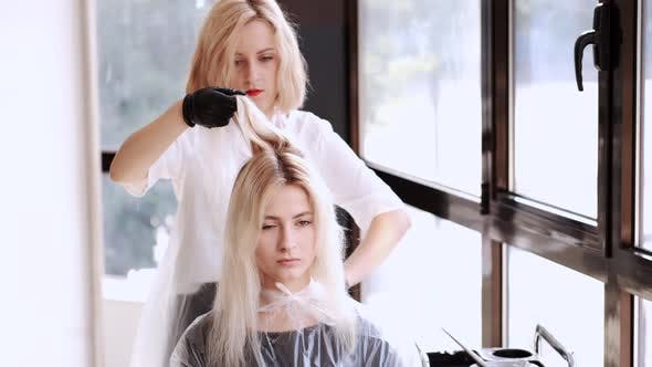 Hairdresser and Client Dyeing Hair in Modern Beauty Salon