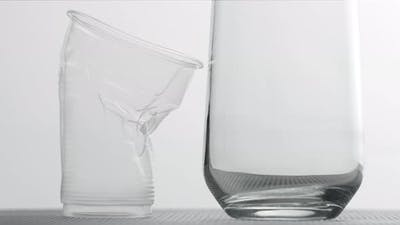 Collapsing Plastic Cup and a Glass on Light Background