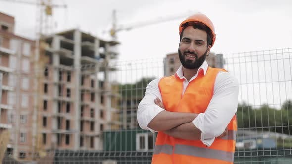 Thumbnail for Portrait of Smiling Architect Man Standing on the Construction Site with Crossed Hands Looking at