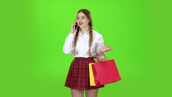 Thumbnail for Schoolgirl Speaks on the Phone and Holds Shopping Bags. Green Screen. Slow Motion