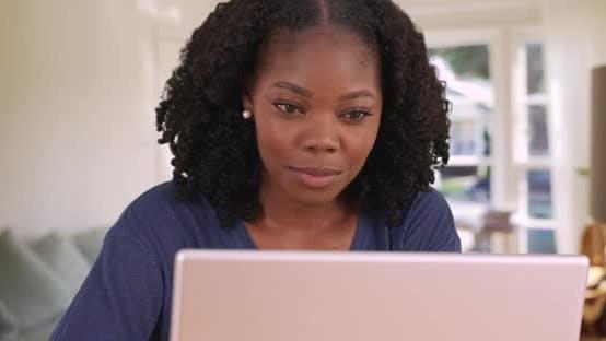 Cover Image for Nahaufnahme von attraktiven lächelnden schwarzen Frau mit Laptop im Haus