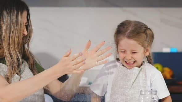 Thumbnail for Daughter and Mother Clap Hands with White Flour at Table