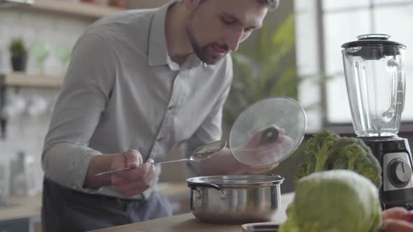 Thumbnail for Handsome Good-looking Man in the Shirt Cooking Soup in the Kitchen. Concept of Healthy Food, Home