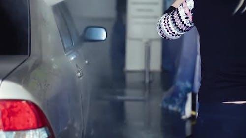 Girl Washes the Car with a Spray Gun