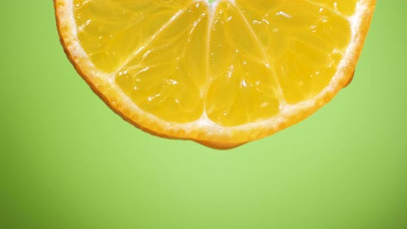 Water Dropping on an Orange Slice , Fruit for Diet and Healthy Food. Green Backgrond