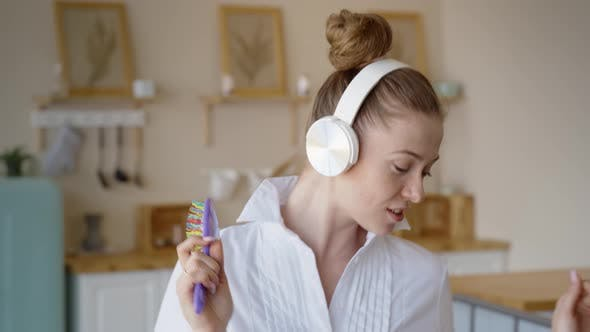 Thumbnail for A Woman Lying on the Bed Listens To Music with Wireless Headphones and Relaxes, The Woman Dances and