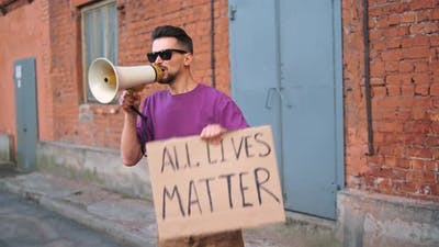 Caucasian Man are Protesting in the Street with Megaphones and Signs