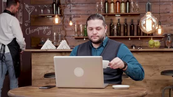 Handsome Man with Long Hair Looking at His Laptop Screen and Drinks Coffee
