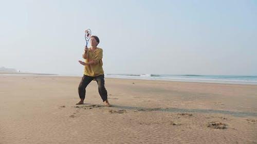 Senior Woman Practicing Tai Chi Balloon Ball on the Beach