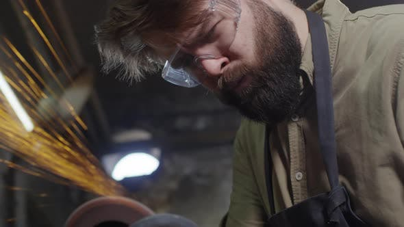 Thumbnail for Handsome Worker Polishing Metal Detail in Smithy