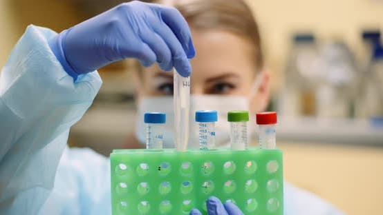 Cover Image for Scientist Holding Tubes at Laboratory in Molecular Biotechnology Laboratory