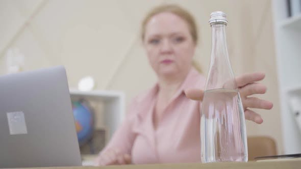 Thumbnail for Blurred Caucasian Woman Taking Bottle of Water and Drinking. Busy Senior Businesswoman Feeling