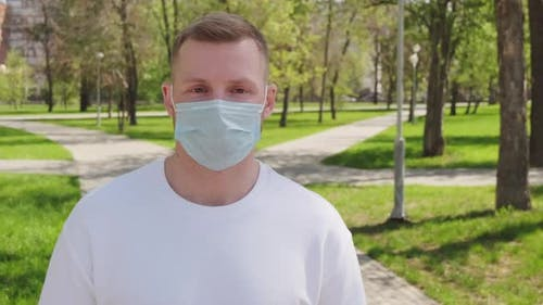 Man in Face Mask Posing for Camera Outdoors