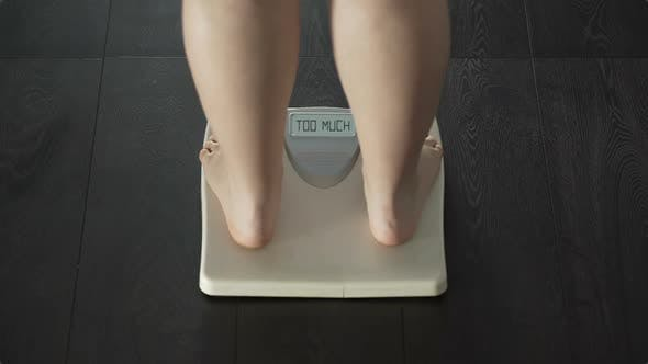 Thumbnail for Female stepping on scales, word too much appearing on screen, overweight, rear