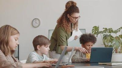 Woman Teaching IT to Diverse Children
