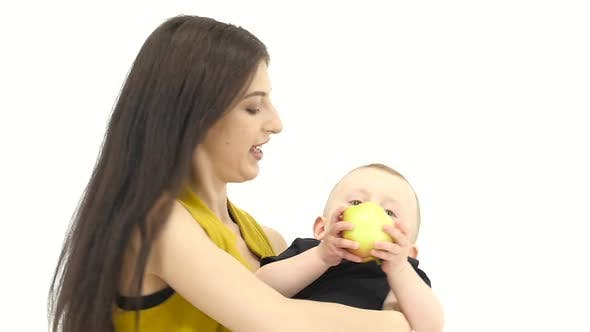 Girl of Throws Her Baby Up, He Likes It Laughs. White Background. Slow Motion