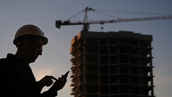 Thumbnail for Engineer at the construction site using his phone texting