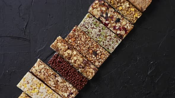 Thumbnail for Various Healthy Granola Bars Placed in a Row on Black Stone Table