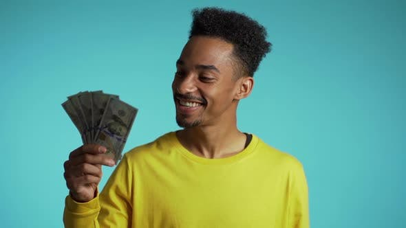 Thumbnail for Satisfied African Man Showing Money - U.S. Currency Dollars Banknotes on Blue Wall.