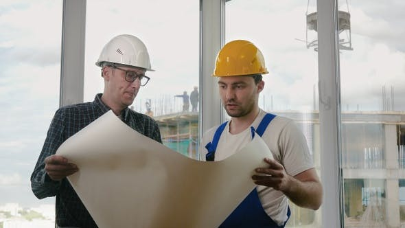 Cover Image for Engineer and construction worker discuss a blueprint.