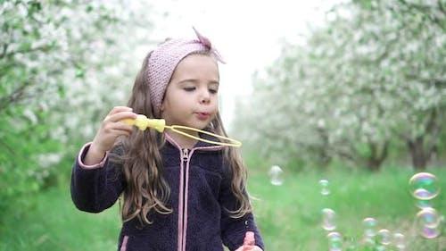 Kleines Mädchen spielen mit Seifenblasen in blühenden Garten, Zeitlupe
