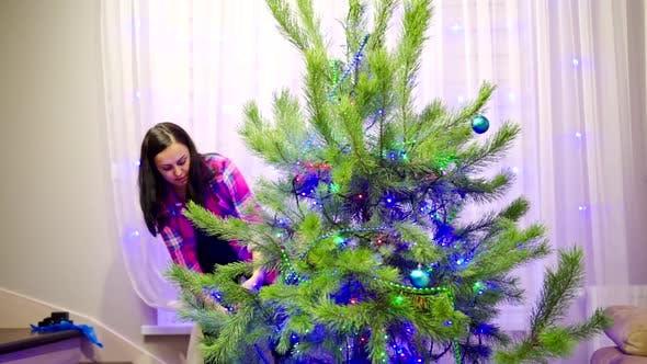 Frau schmückt Weihnachtsbaum. Junge Frau schmückt Weihnachtsbaum