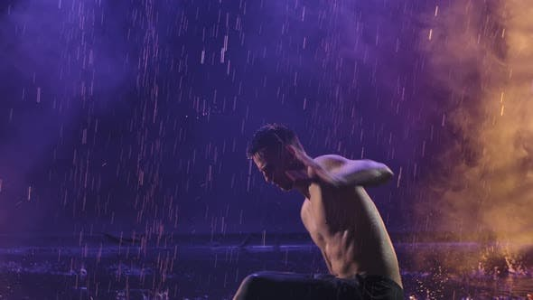 Thumbnail for A Man Practicing Capoeira in a Dark Room Among Raindrops and Splashing Water. Smoky Background with