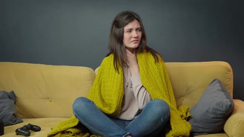 Sick Girl Sits on Yellow Sofa Coughing Suffering From Sore Throat or Angina