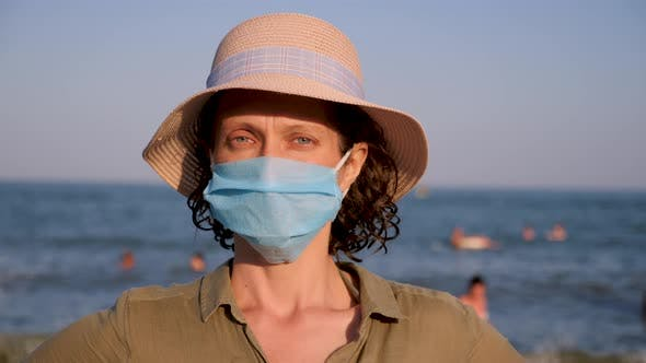 Portrait of beautiful woman in panama wearing disposable mask. Epidemic contagious virus