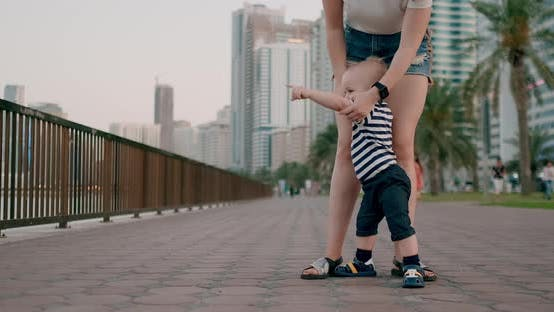 Thumbnail for Smiling Happy Laughing Baby Takes First Steps in Summer on the Waterfront