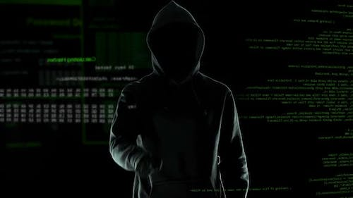 Hacker makes threatening gesture into the camera, cyber attack and blackmail