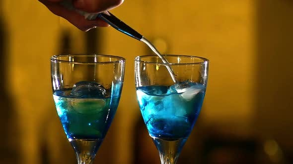 Thumbnail for Barman Making Cocktails at the Night Club, Using Two Glasses with Ice Adding Cloudy White Liquid