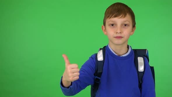 Thumbnail for A Young Cute Boy with a Schoolbag Smiles and Shows a Thumb Up To the Camera - Green Screen Studio