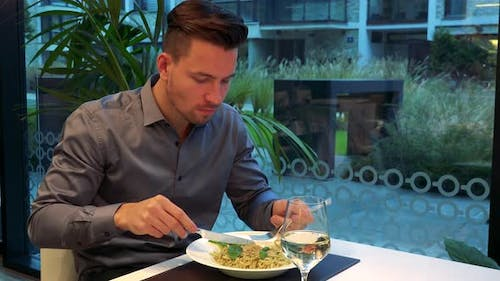 Young Man Sits in the Restaurant and Eats Meal Pasta