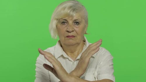 An Elderly Woman Shows a Stop, Forbidden Gesture. Old Grandmother. Chroma Key