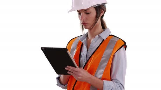 Thumbnail for Woman wearing orange vest and hardhat working on tablet on white background