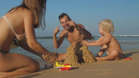 Parents Enjoy Leisure Time Making Hills From Sand on Beach