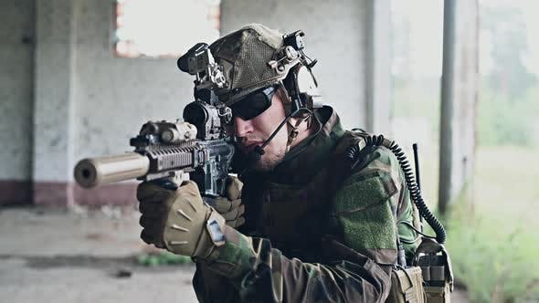Stabilized Shot of Soldier in Camouflage Aiming Assault Rifle and Running Inside Building