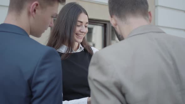Cover Image for Young Woman and Two Men in Formal Wear Discussing Documents on the Terrace. Business Relationship