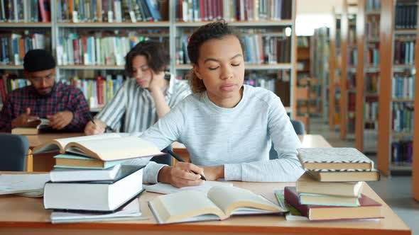 Tired African American Girl Studying in College Library Writing Reading Books