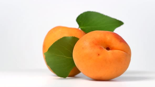 Apricots rotating on white background